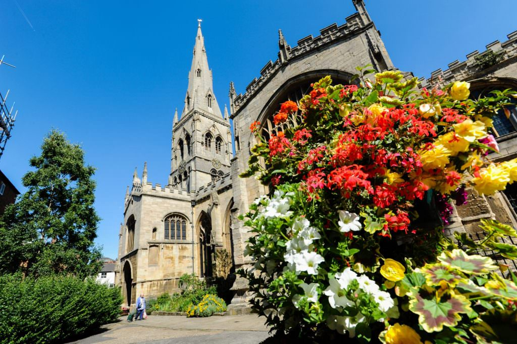 Image shows a church on a sunny day, with flowers in the foreground.