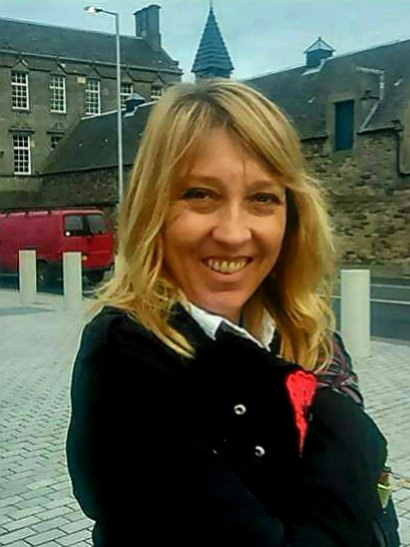 Image shows Listening Line Coordinator, Tracey Parr. She is stood, smiling at the camera and is wearing a black coat.