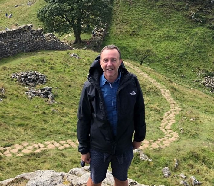 Image shows Community Engagement and Development Officer, Andrew Oxnard. He is hiking in the countryside.