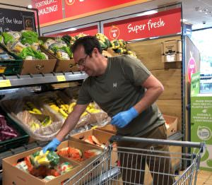 Image shows a volunteer (a man), shopping in a supermarket.