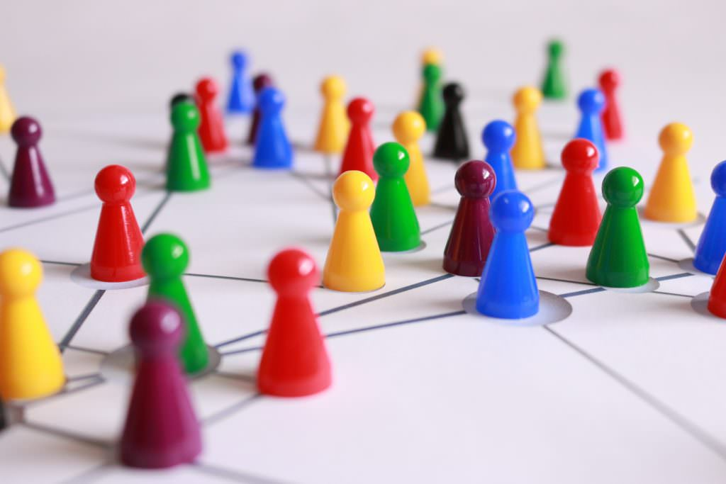 Image shows multi-coloured board game pieces on a white sheet of paper with connecting lines.