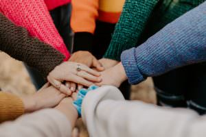Image shows a close up of lots of hands all joined together.