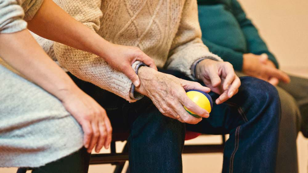 Image shows a close up of a lady's hand, holding an older man's hand. He is holding a colourful ball in his hand.