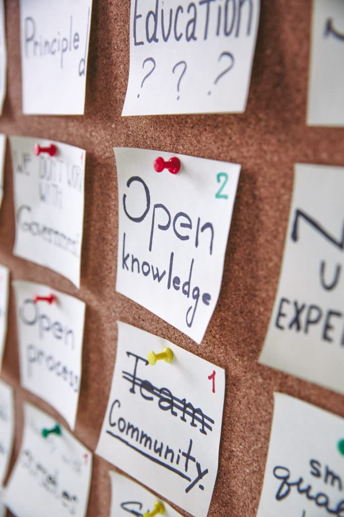 Image shows a notice board, with post-it notes, with words like community and open knowledge.