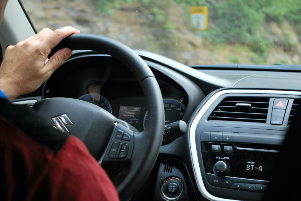 Image shows a close up of someone driving a car. they have their hands on the wheel.